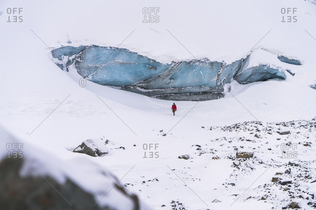 Mid distance view of hiker walking on snow covered landscape