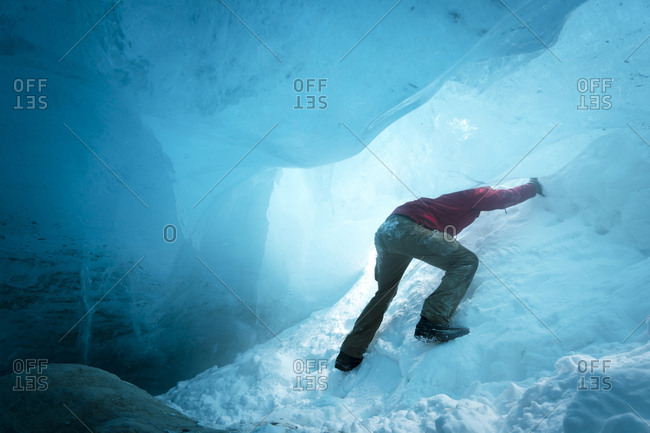 Low angle view of hiker ice climbing in cave