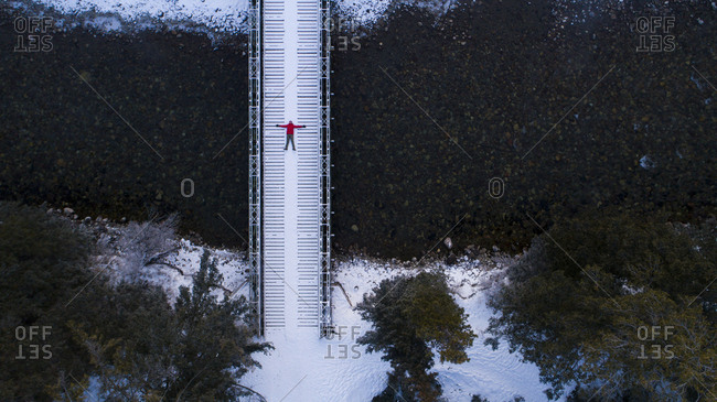 Mid distance view of hiker lying on footbridge in forest during winter