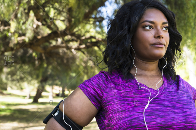 Confident woman looking away while listening music at park