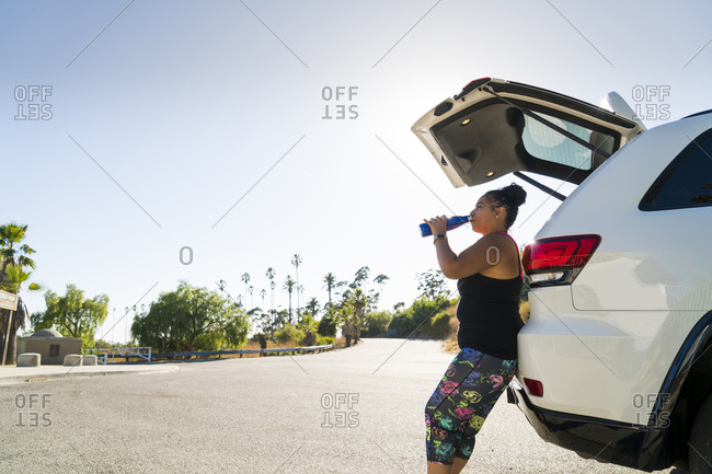 Side view of sportswoman drinking water while leaning against car