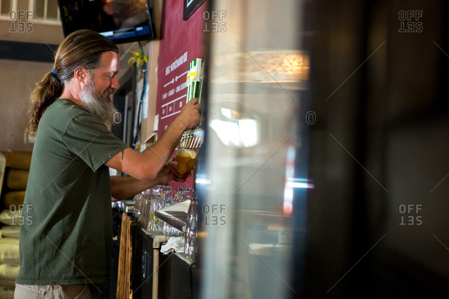 Side view of man pouring beer from tap