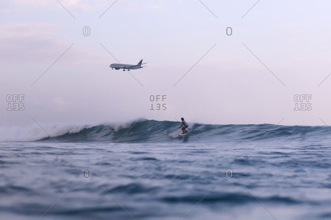 Airplane flying over surfer in sea