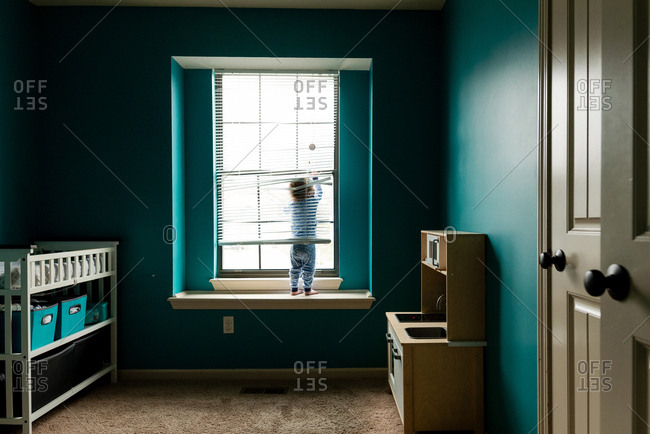 Rear view of boy playing with window blinds while standing on sill at home