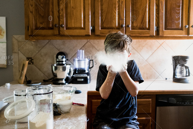 Boy playing with flour while sitting in kitchen