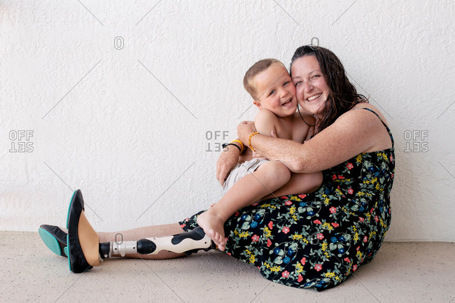 Portrait of mother with prosthetic leg embracing son while sitting against wall
