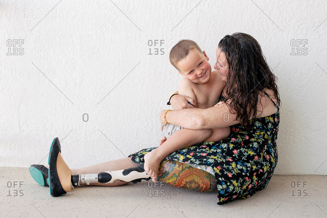 Mother with prosthetic leg embracing son while sitting against wall
