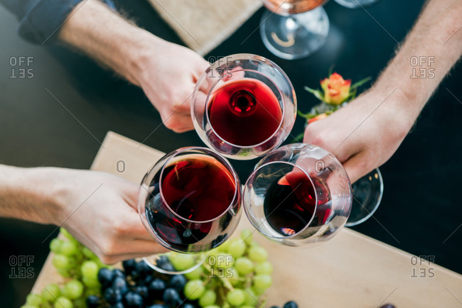 Cropped hands of male friends toasting wine at tasting room