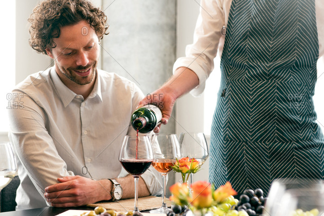 Midsection of bartender pouring wine for customer at table in tasting room
