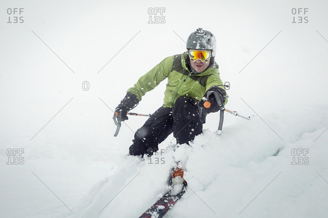 Male skier carving a turn in the snow in near white out conditions