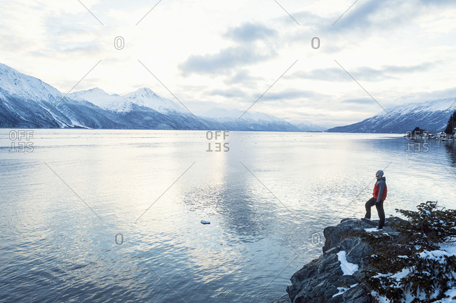 Young man standing on rocks viewing the water and mountain scenery around him