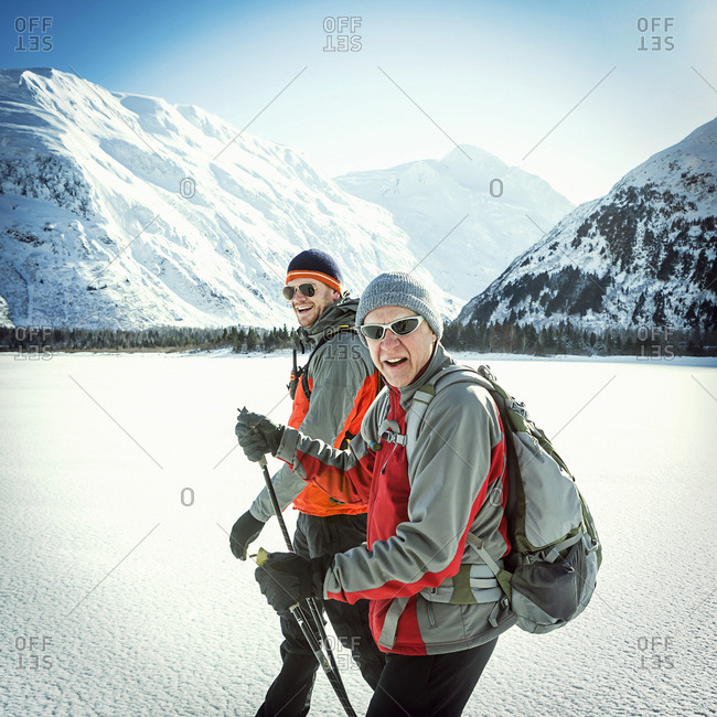 Father and adult son hiking across a snow covered frozen lake