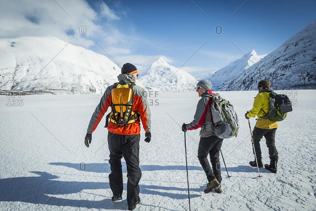 Father and two adult sons hiking away across a snow covered frozen lake