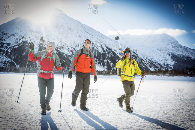 Father and two adult sons hiking across a snow covered frozen lake