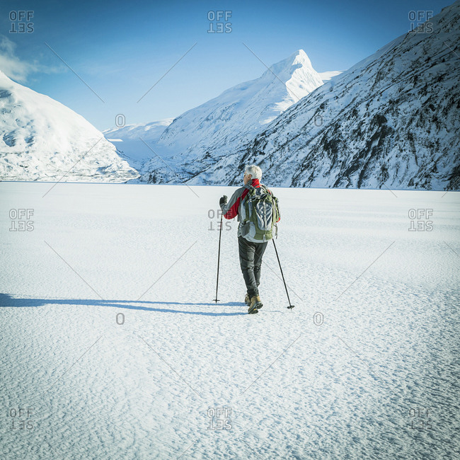 Mature man hiking away across a snow covered frozen lake