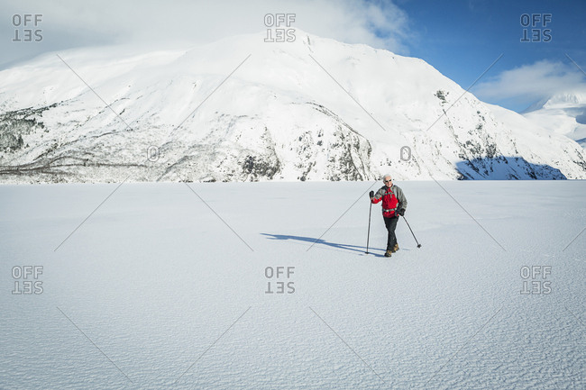 Mature man hiking across a snow covered frozen lake