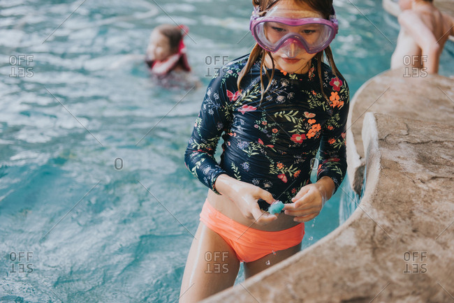 Girl in snorkel mask standing in pool