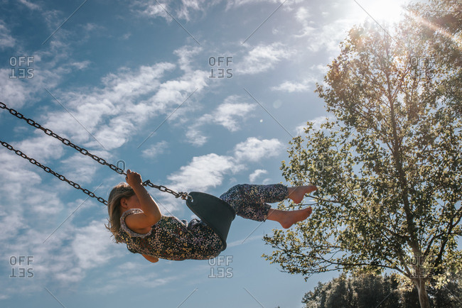 Girl on a swing in sunlight