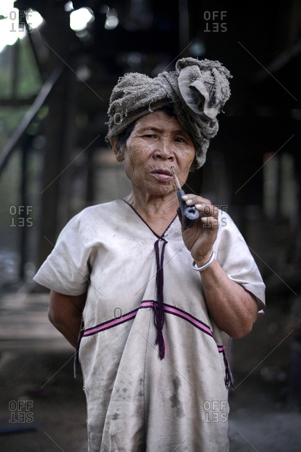 Kanlaya Niwattana, Chiang Mai, Thailand- 2014. A Karen hill tribe old woman holding up a smoking pipe, wearing white means that she is still single.