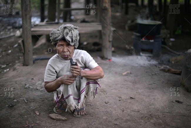 Kanlaya Niwattana, Chiang Mai, Thailand- 2014. An old Karen hill tribe woman holding up a smoking pipe, wearing white means that she is still single.