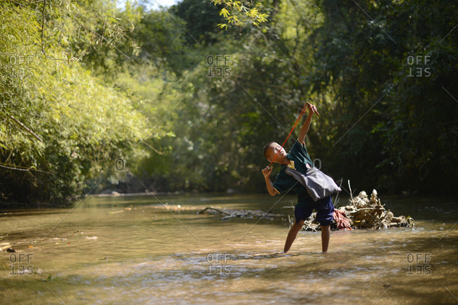 A Karen hill tribe boy is pulling a slingshot on the small river in Kanlaya Niwattana, Chiang Mai, Thailand - 2014.