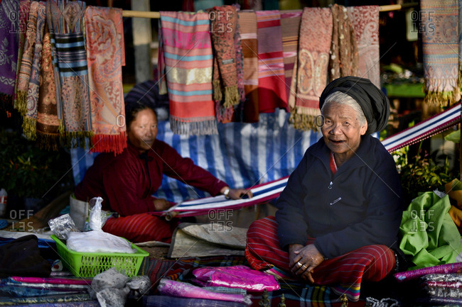 Palong hilltribe women weaving and selling shawls at the evening local market in winter up in Doi AngKhang, Chiang Mai, Thailnad - 2013.