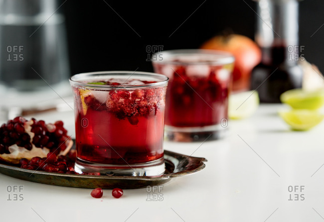 A cocktail with fresh pomegranate on a silver tray