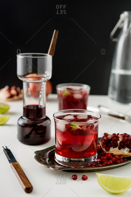 Preparing a cocktail with pomegranate and lime