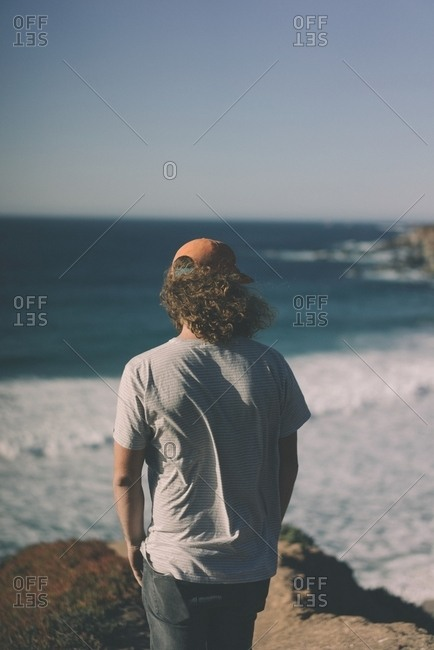 Man with long, curly hair standing on a windy beach