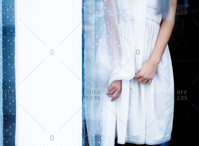 Woman in a white dress clutching a sheer white curtain