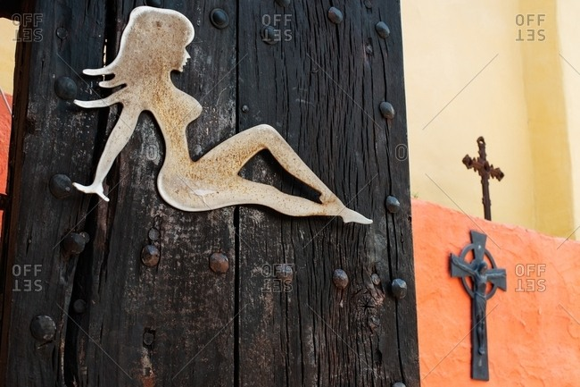 Silhouette of a sexy woman on an aged wooden post
