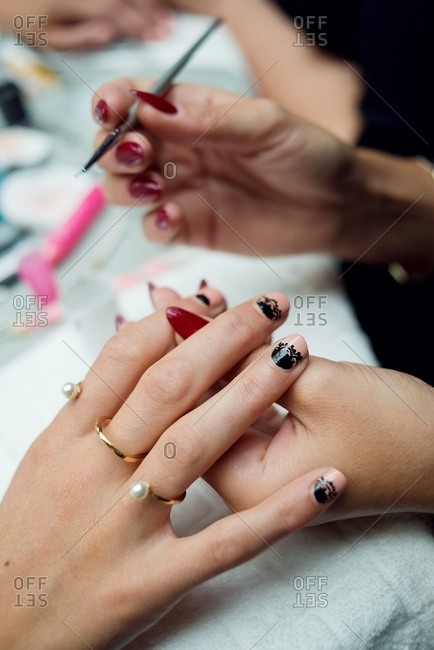 Stylist painting elaborate designs on a woman's fingernails