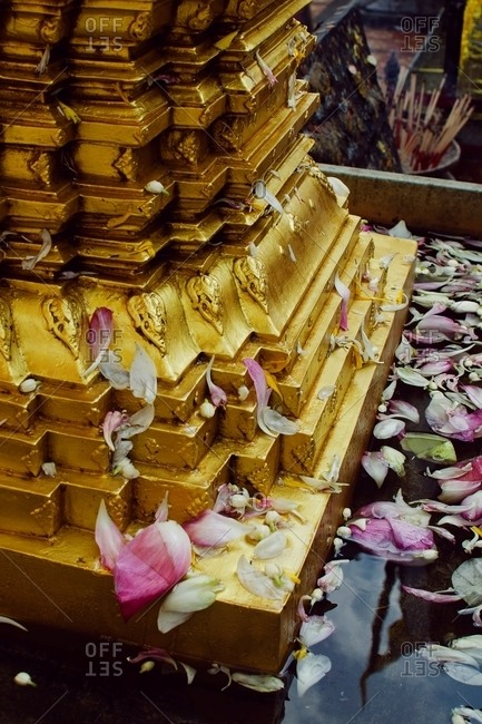 Flower petals at the base of a carved gold column in water
