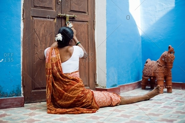 Woman in a sari sitting outside of a door unlocking a padlock