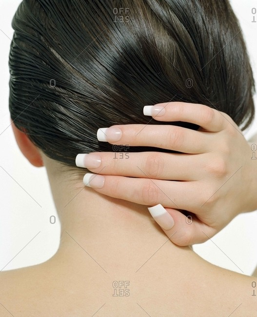 Woman with a French tip manicure holding her brunette hair