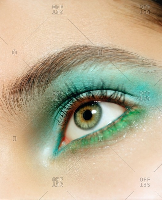 Eye of a woman with green eyeliner and turquoise eyeshadow