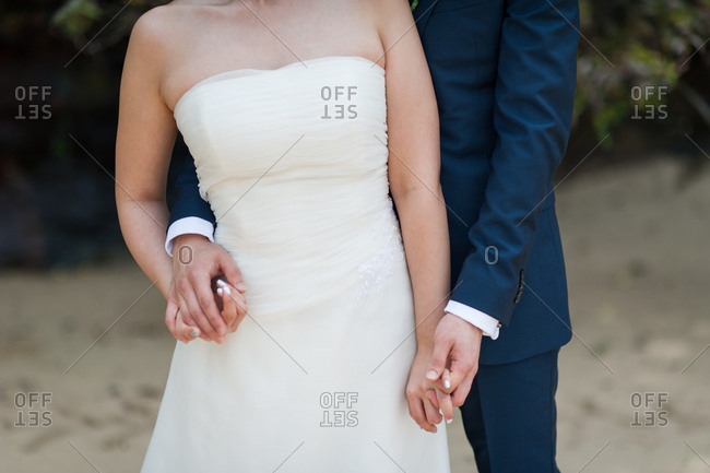 Groom in a blue tux embracing his wife in a strapless gown