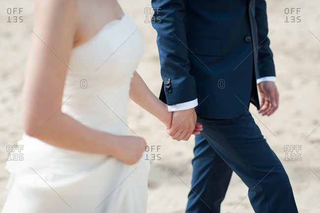 Bride and groom holding hands and walking together on a beach