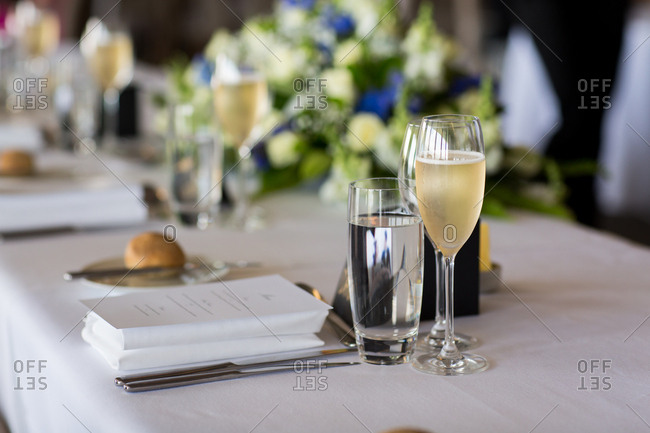 Place setting with a menu and champagne at a wedding reception