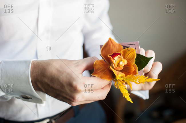 Hands of a groom holding an orange orchid boutonniere