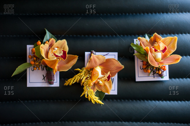 Three orange orchid boutonnieres on a black leather surface