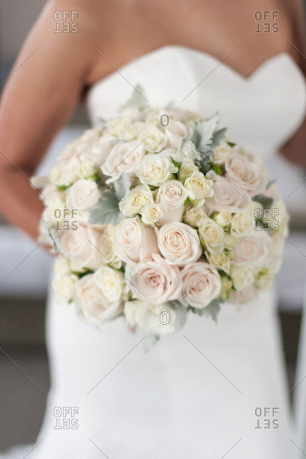 Bride in a strapless gown holding a bouquet of light pink and white roses