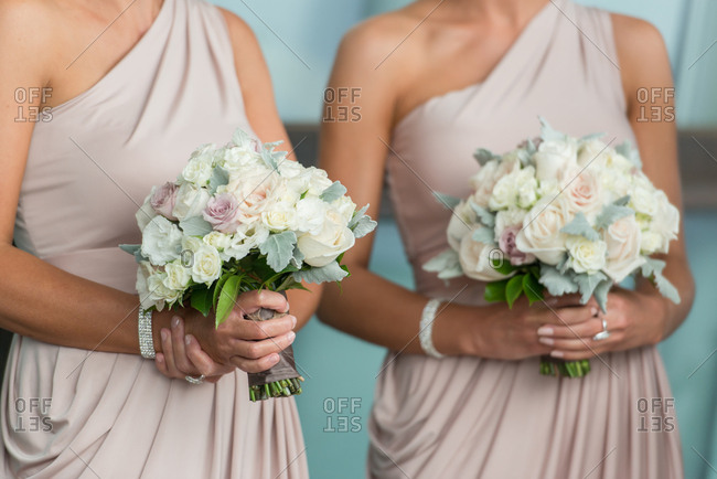 Two bridesmaids in one-shoulder dresses holding bouquets