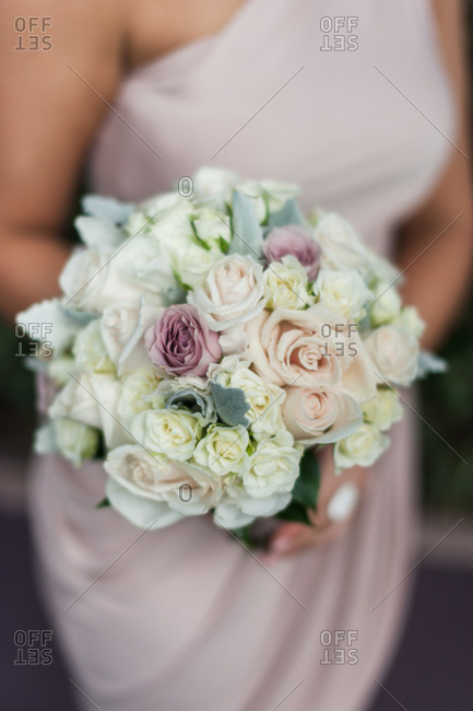 Bridesmaid in a one-shoulder dress holding a bouquet of flowers
