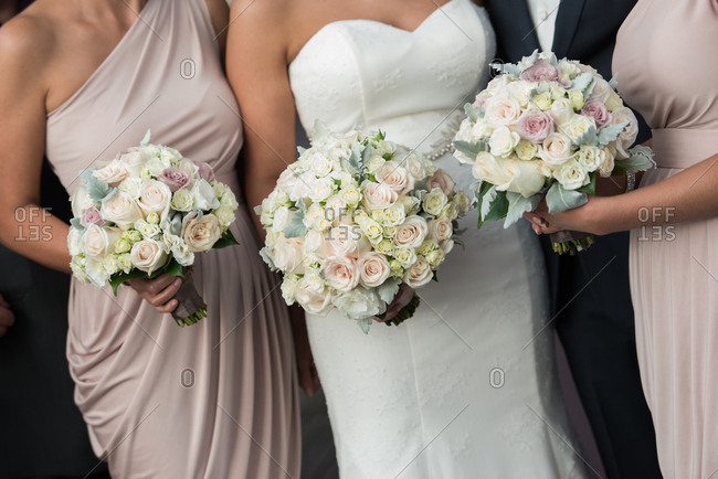 Bridesmaids in pastel dresses standing with a bride and groom