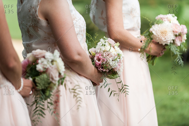 Bridesmaids in light pink dresses holding bouquets