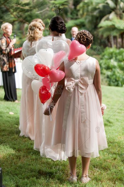 Bridesmaids at an outdoor wedding holding heart-shaped balloons