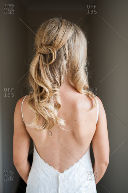 Bride in a backless gown with long, loose curls