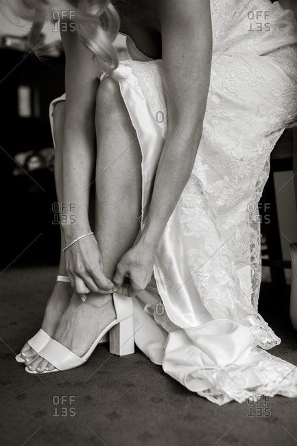 Bride fastening the strap on her shoes before a wedding