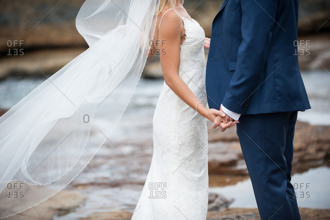 Bride and groom standing on a rocky beach holding hands